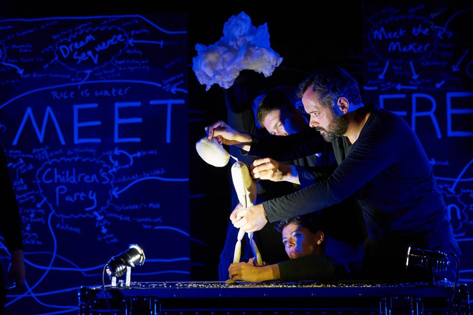 Two actors hold a puppet on a stage.
