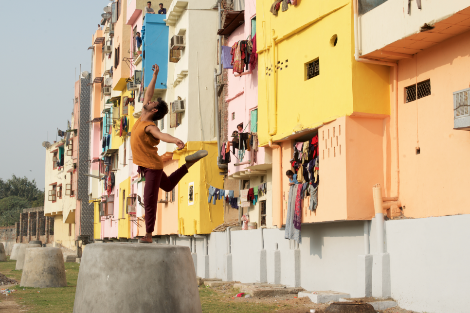 Dancer in front of colourful houses in Delhi