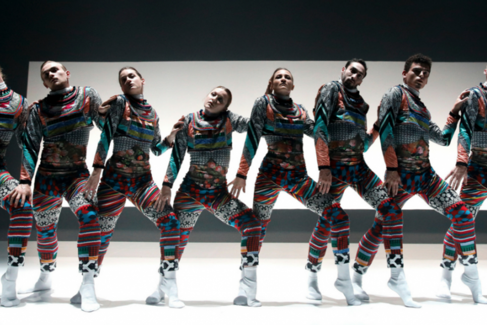 8 dancers lined up on stage in colourful bodysuits