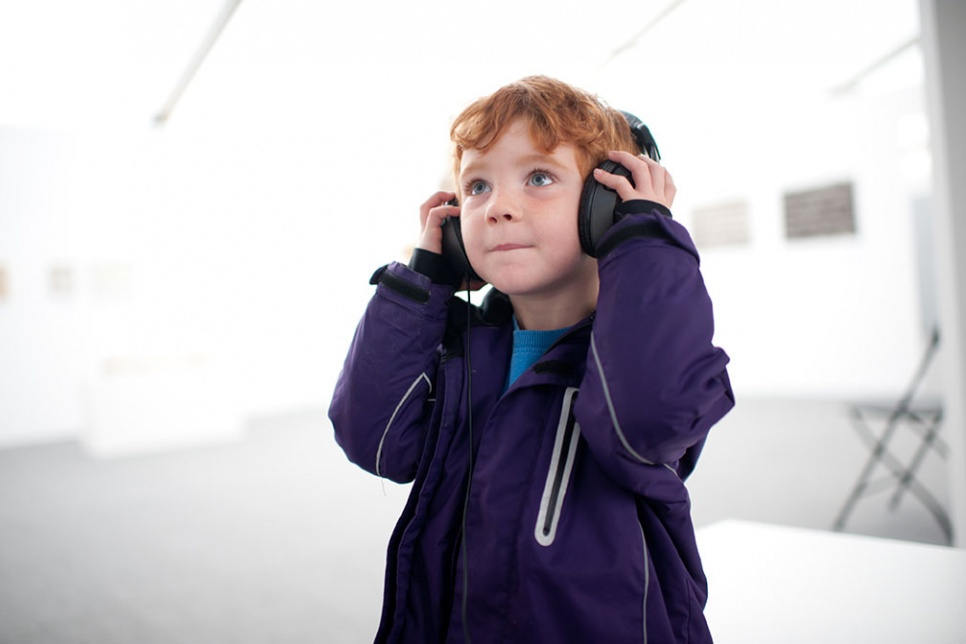 Boy with headphones on stands in a white gallery