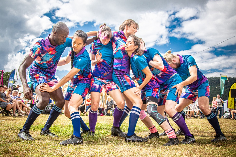 Performers pose as a rugby team in a scrum
