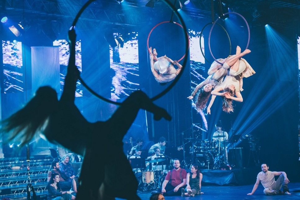 Circus performance with suspended hoops and acrobats
