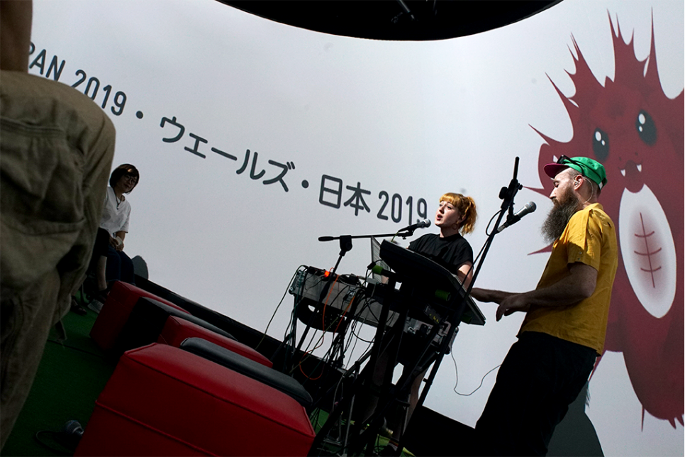 A male and female musical performance. Singing and playing keyboards in front of a large screen containing a cartoon character and Japanese writing