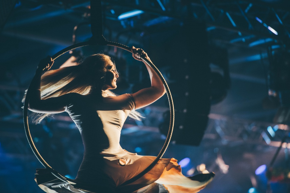 Aerial performer spinning on hoop with blue stage lighting