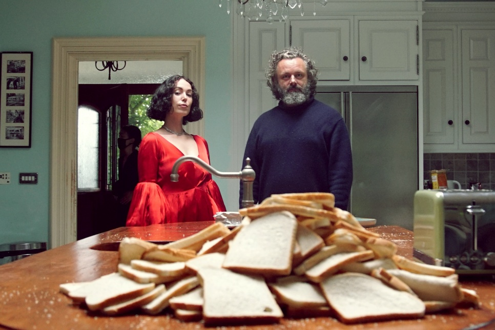 Kelly Lee Owens & Michael Sheen stood in a kitchen behind a large pile of bread