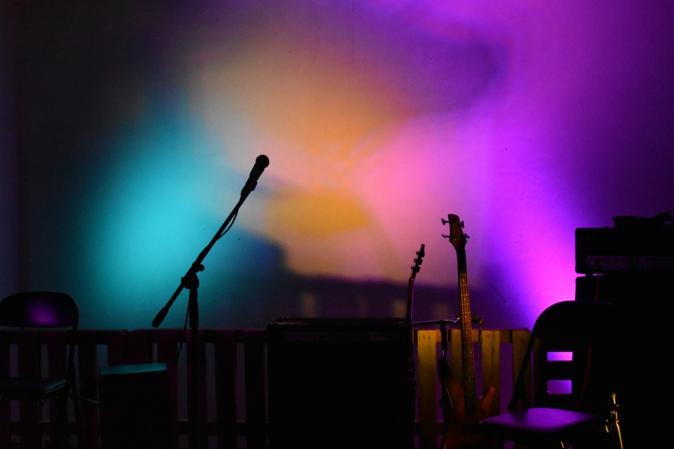 Multicoloured stage lights with silhouettes of microphone & instruments
