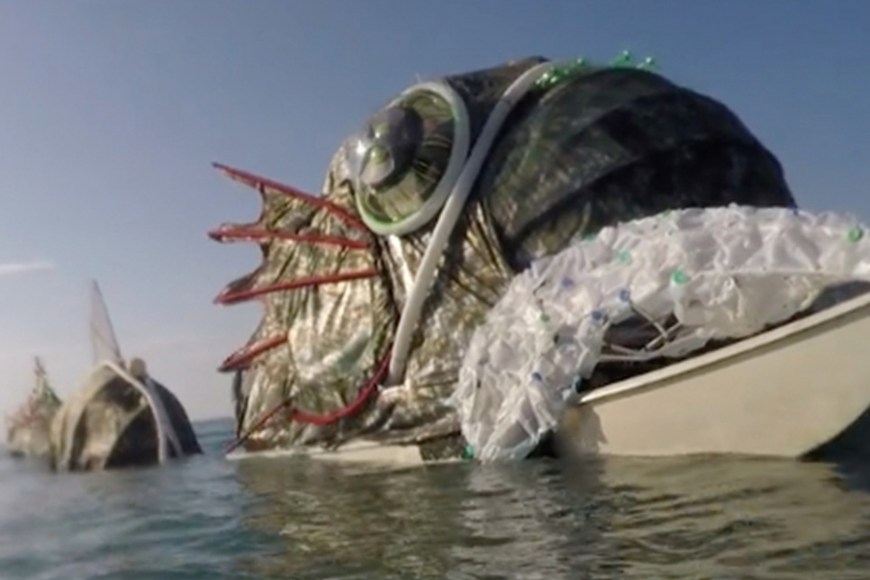 Large fish sculpture in the sea made out of rubbish